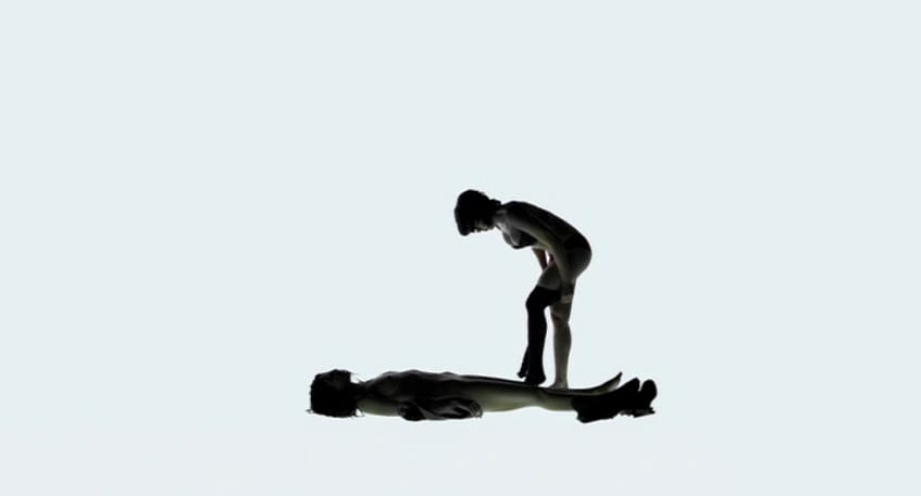 In a white room a woman removes the clothes of a dead woman