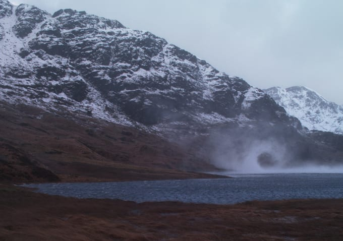 a Loch in Scotland with mist blowing over it in a wave