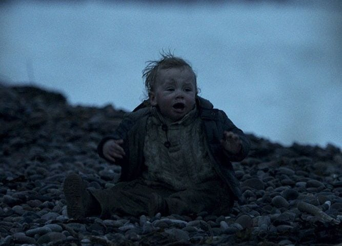 a baby on a beach crying