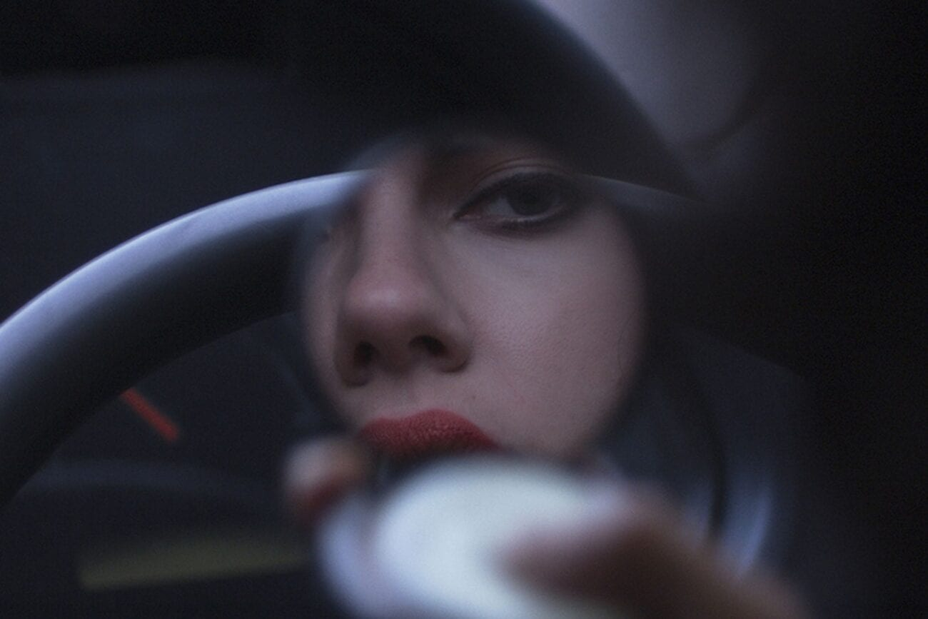 The woman looks at herself in a hand mirror while applying lipstick