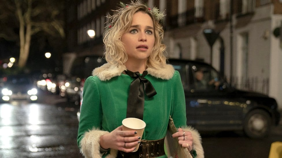 Emilia Clarke in her elf costume in Last Christmas, standing in the street with a cup of coffee, looking into the distance in dismay