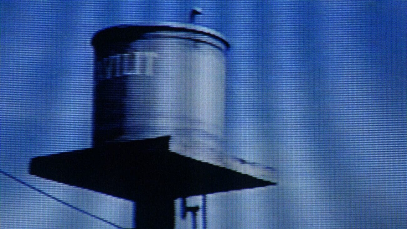 A medium shot of news coverage focusing on a water tower displayed on a television screen.