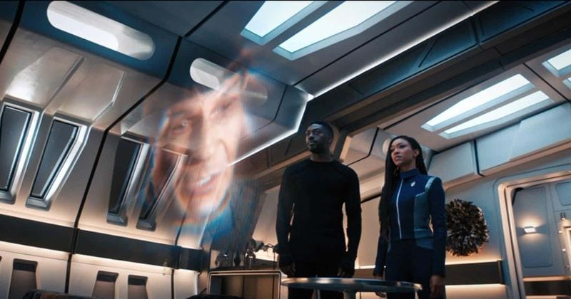 Burnham (Sonequa Martin-Green) and Book (David Ajala) look up at hologram of Spock (Leonard Nimoy)