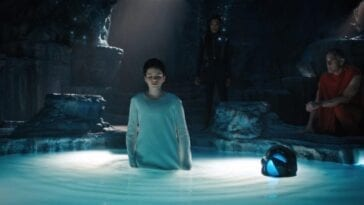 Adira Tal (Blu Del Barrio) in a white gown standing in a lighted pool with water up to their waist while a Trill elder in a red kneels to the right