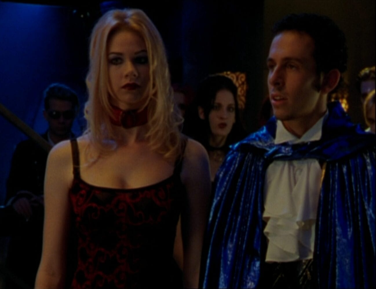 Wearing a dark red dress and a choker, Chanterelle stands in the club with Diego, who wears a ruffled shirt and blue cape, and the rest of the vampire cult, also dressed in vampire attire