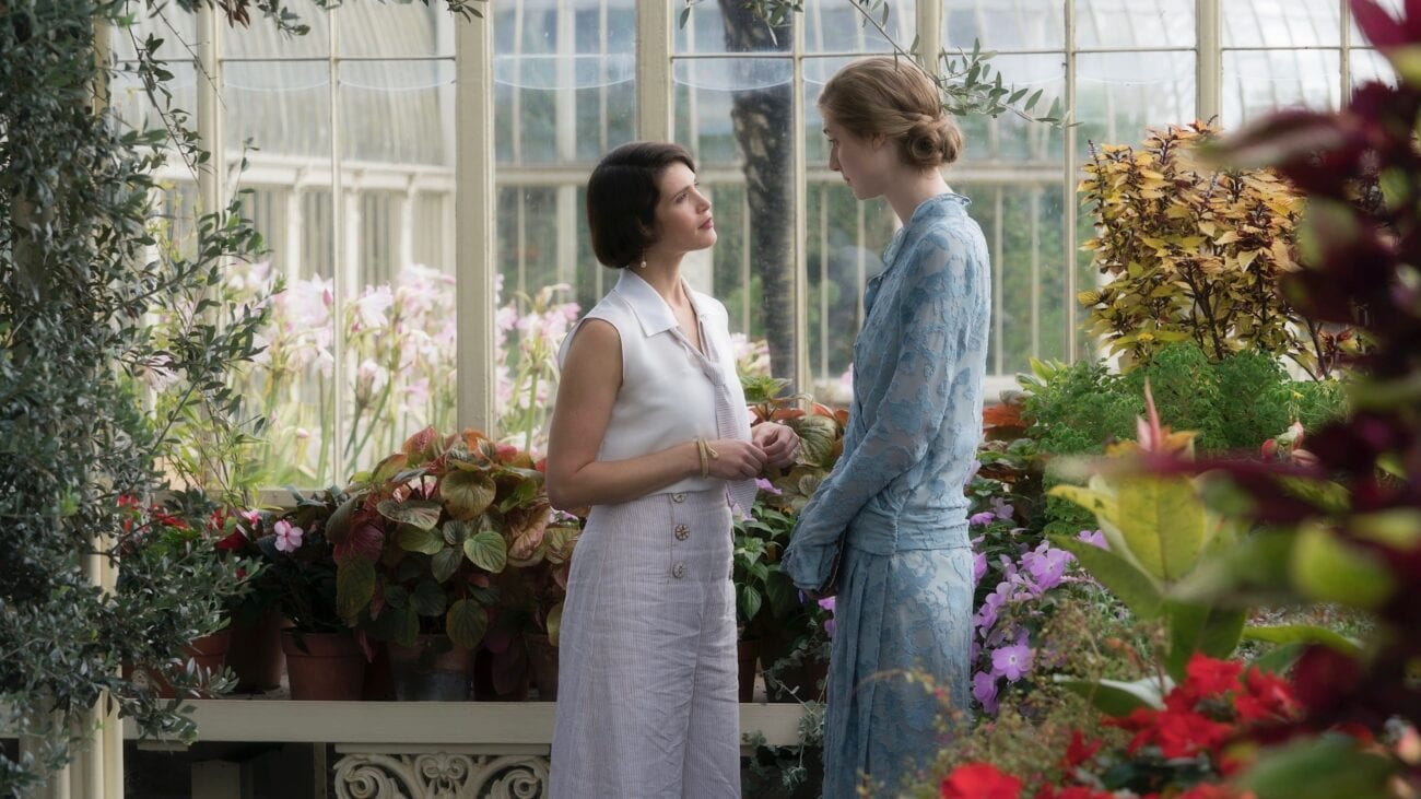 Vita and Virginia stand in a large glasshouse. They are surrounded by flowers and are looking at each other