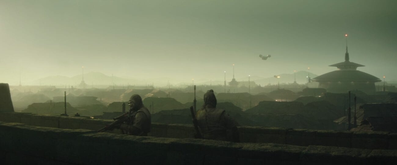 The Razor Crest flies over the town of Calodan, with two guards on the city wall