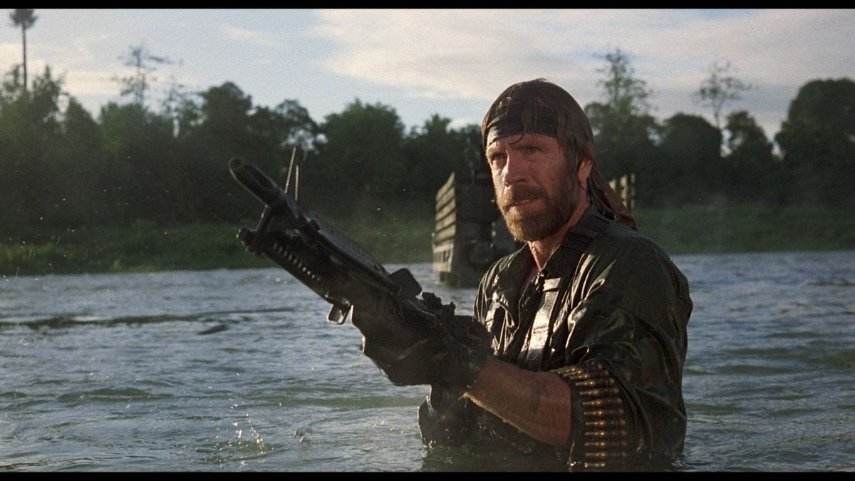 Chuck Norris holding a massive machine gun in a lake in one of many Rambo homages that went straight to video in the '80s