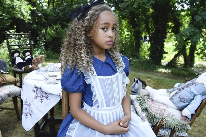 Alice stares into the camera while sitting at a table set up for a tea party