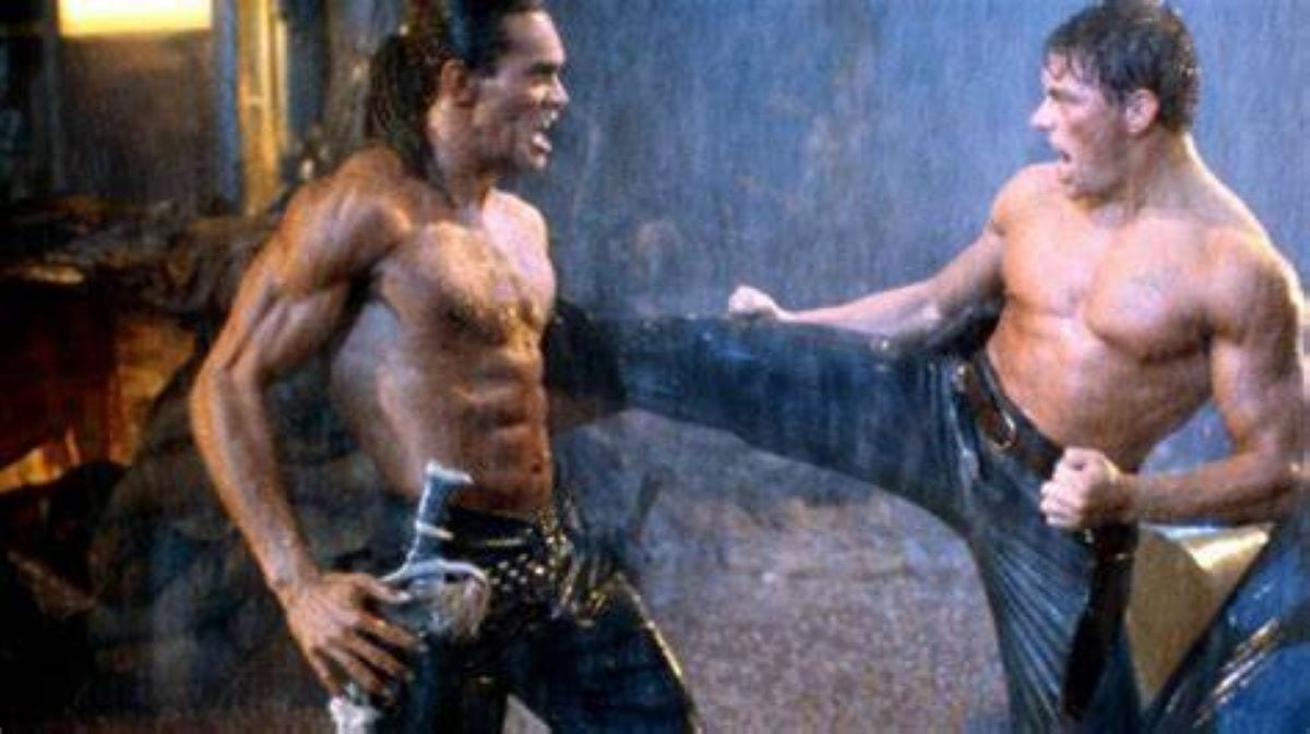 Jean Claude Van Damme launches a kick at the muscular villain in the straight to video Cyborg