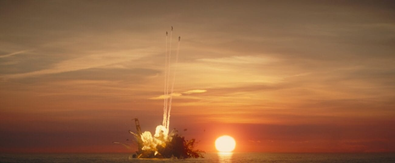 Three Mandalorians fly from the Quarren ship as it blows up, with a sunset in the distance