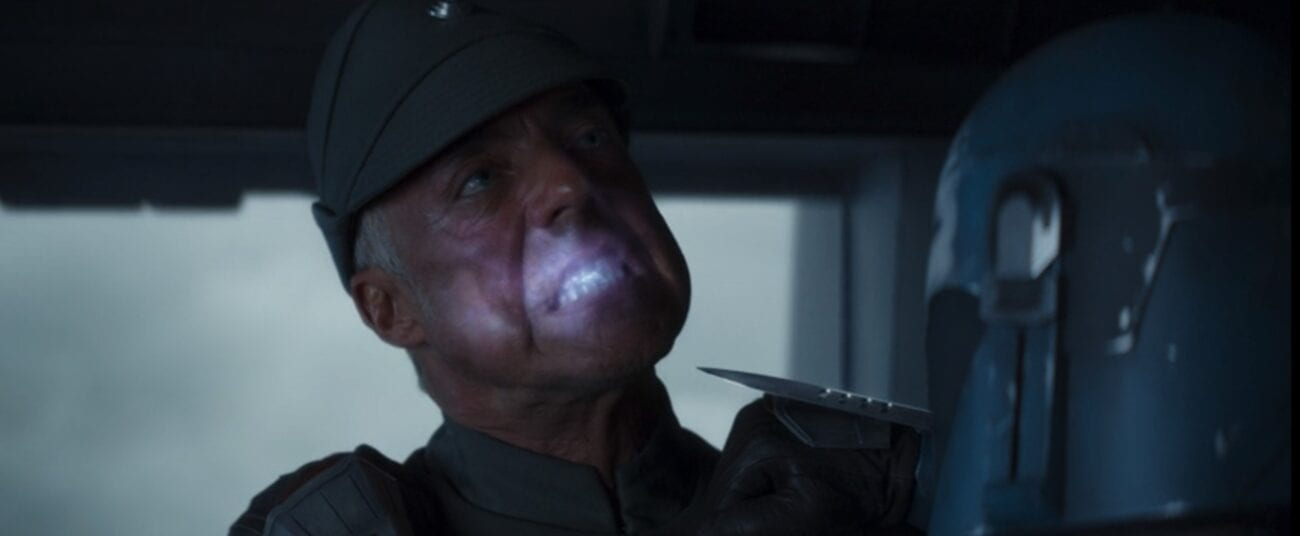The Imperial captain bites an electric suicide pill, while Bo-Katan holds a knife to his throat