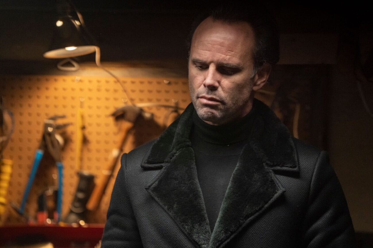The assassin in his turtleneck and jacket looks down on his captive in a garage.