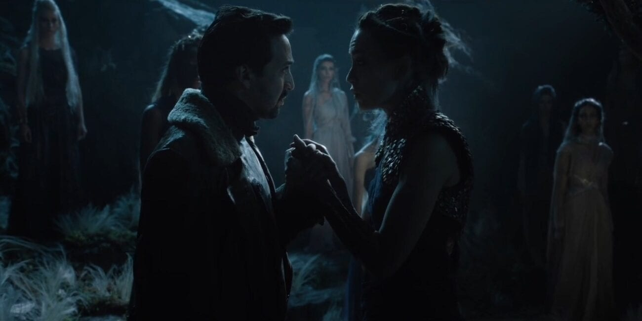 His Dark Materials - Lee and Serafina clasp hands facing each other as several other witches look on