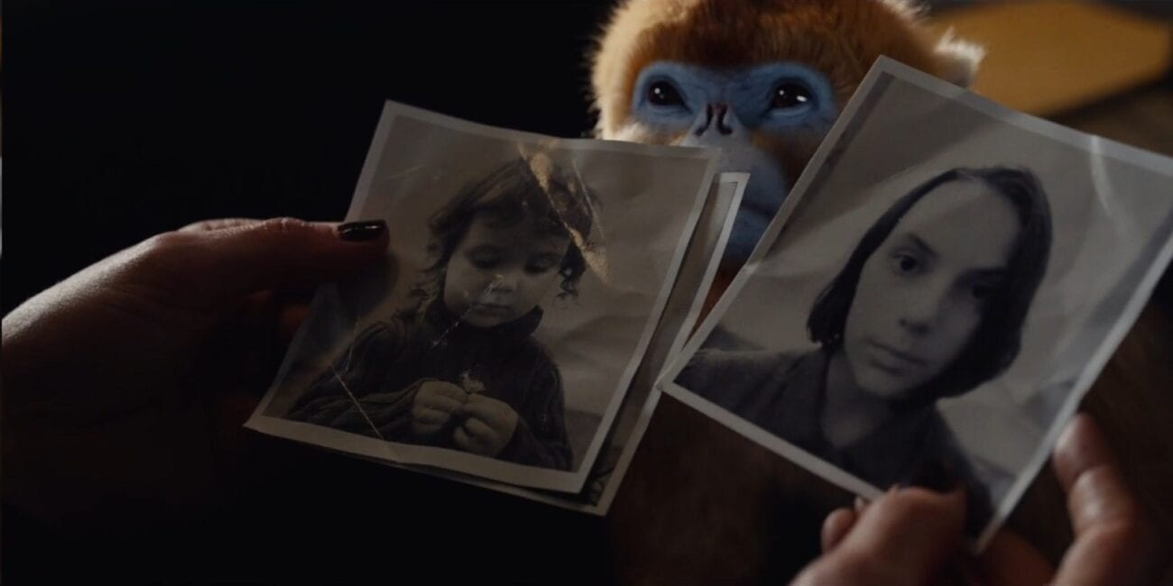 His Dark Materials - Mrs. Coulter's hands leaf through black and white photots of a younger Lyra, as her monkey demon looks on