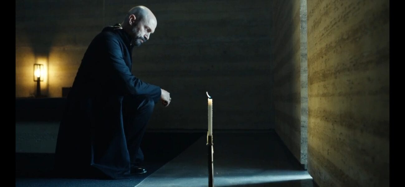 MacPhail and his dæmon kneel in front of a candle