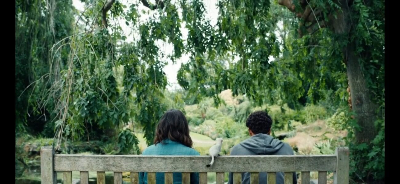 Lyra, Will and Pan sit on a bench in a lush garden