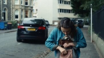 His Dark Materials - Lyra looks in her satchel as a car drives away behind her