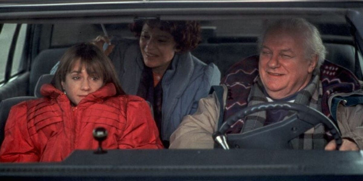 Claudia hiding in her jacket while her parents talk to her as they're driving in the car in Home for the Holidays