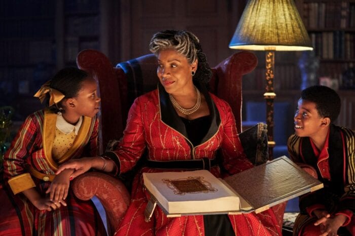 The seated grandmother begins to read a long storybook to her two flanking grandchildren.