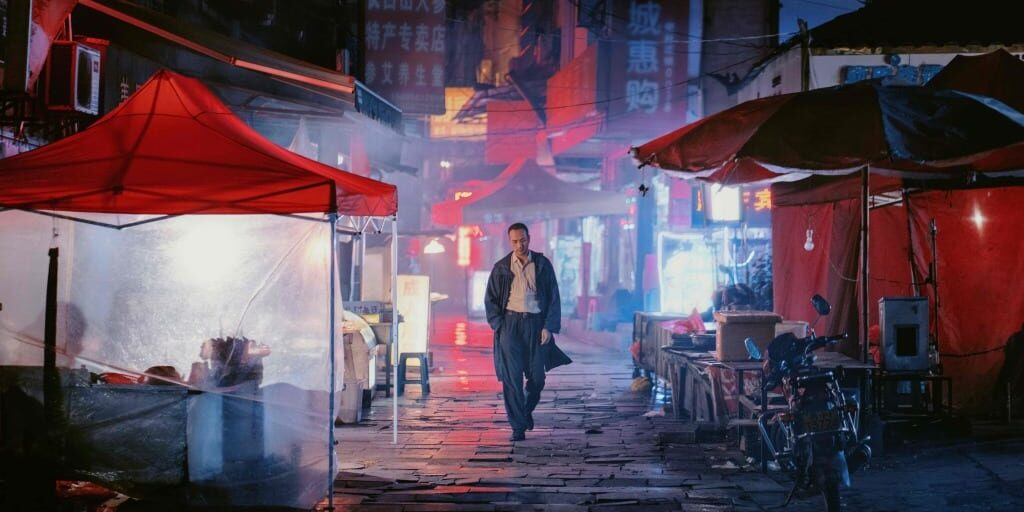 Luo stands in the center of a dark marketplace shrouded in light from the surrounding stands