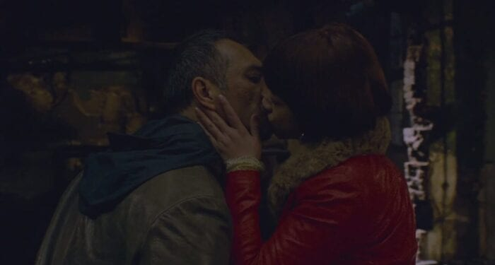 Luo in a brown jacket and Wan in a red jacket embrace and share a kiss, Wans hand tenderly placed on Luos face