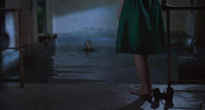 Wans legs and the skirt of her dress show in the foreground as she waits Luos reemergence from the pool of freezing water