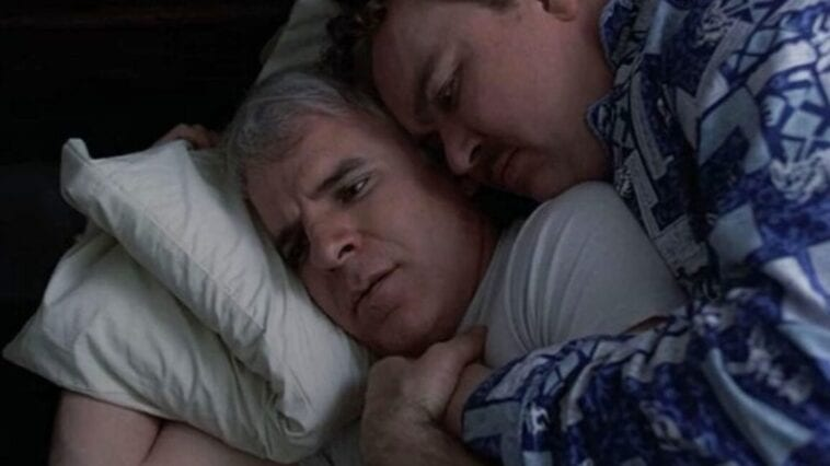 Neal and Del, cuddled together in bed, Neal slightly awake and instantly horrified in Planes, Trains and Automobiles