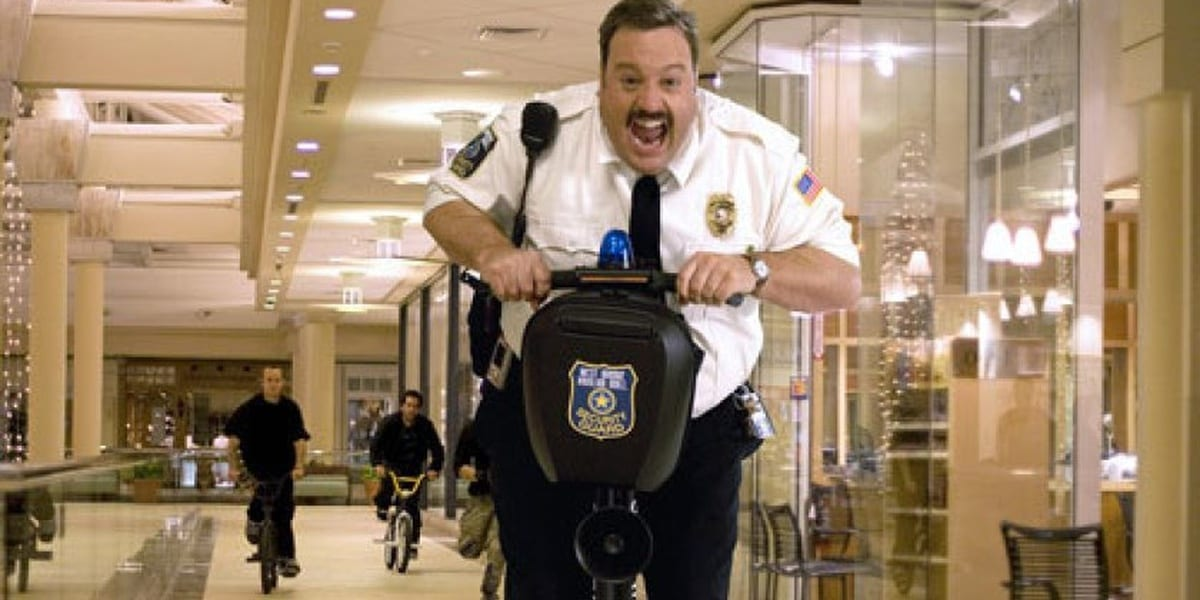Paul Blart being chased by thugs in a mall while riding a Segway