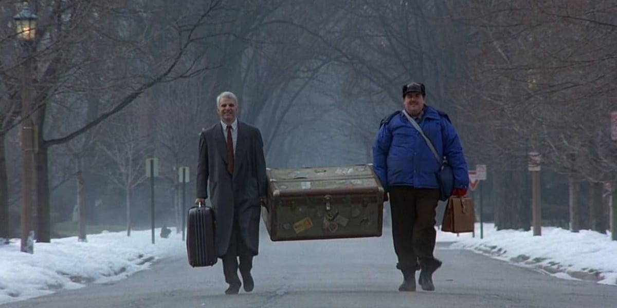 Neal and Del walking down a snowy street while carrying a trunk between them in Planes, Trains and Automobiles