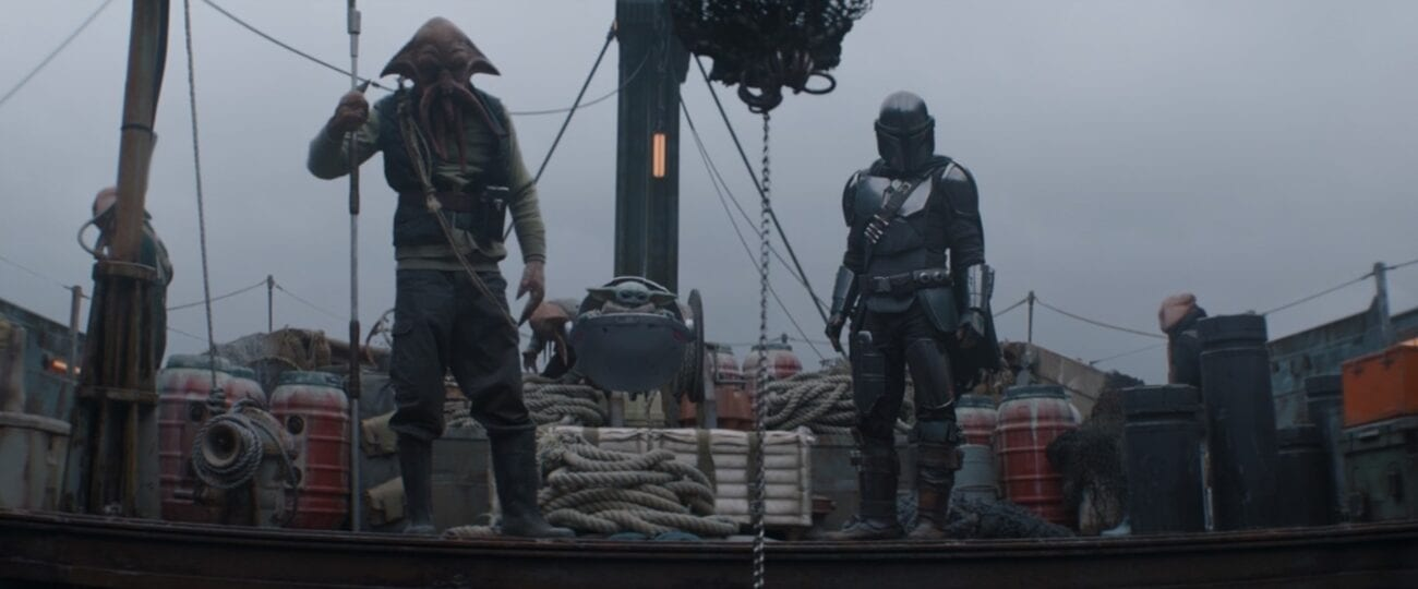 A Quarren alien, The Child (Baby Yoda), and The Mandalorian stand on the deck of a ship