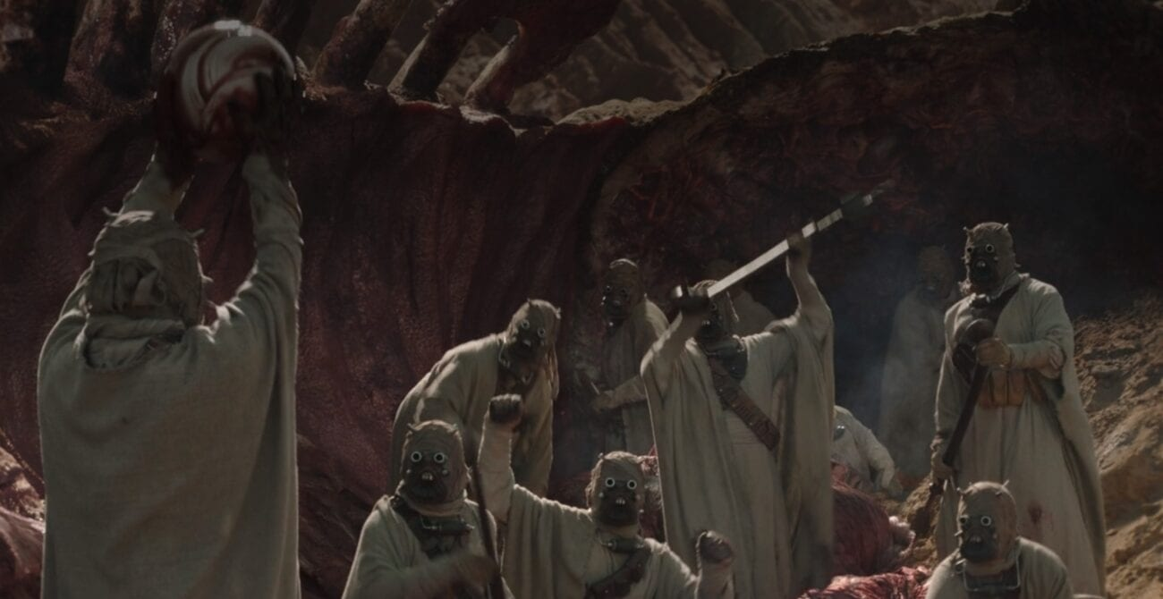 Tusken Raiders celebrate as one holds a newly found krayt pearl over his head