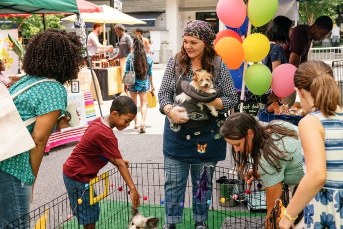 Carol works at dog adoption event with young children.