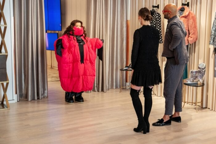 Carol tries on a ridiculous red puffy outfit in front of two boutique managers