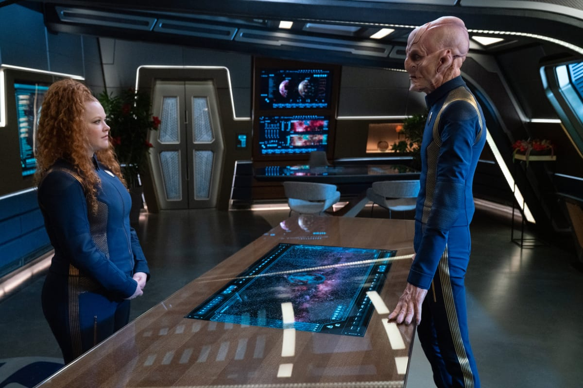 Tilly (Mary Wiseman) looks at Captain Saru (Doug Jones) over a reflective table in his ready room