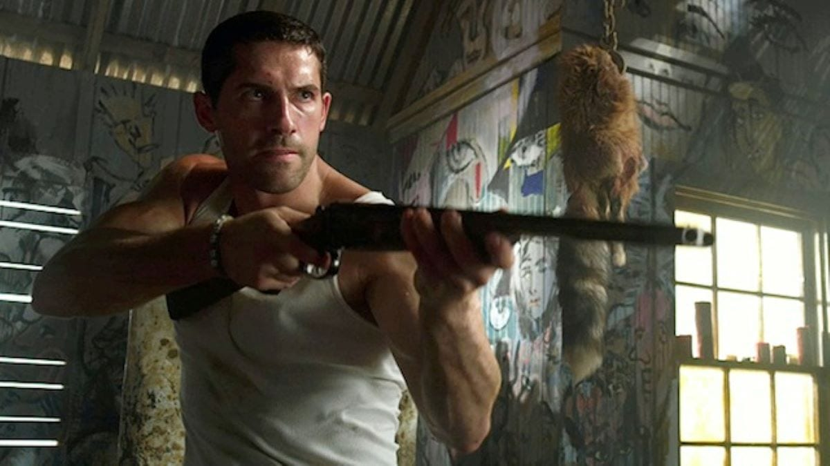 Current low budget action king Scott Adkins holds a shotgun in a warehouse
