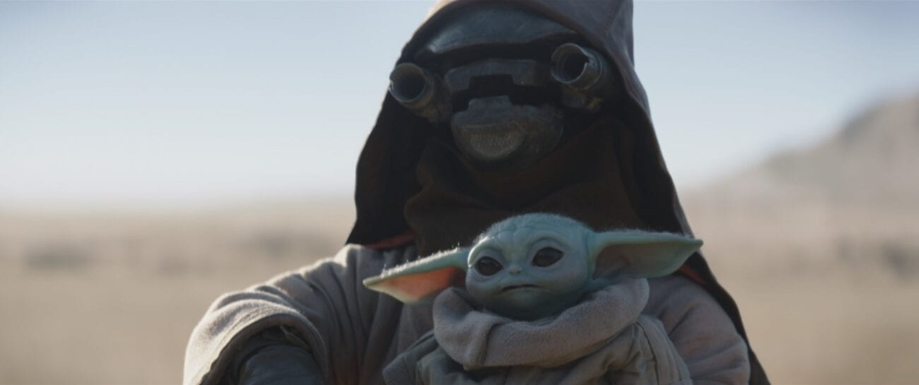 A scrapjaw alien holds The Child (Baby Yoda) threateningly
