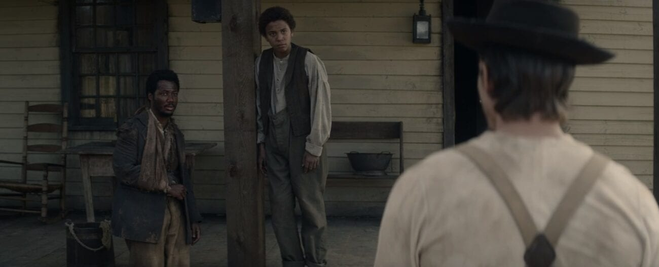 Bob (Henry Pont-Du Jour) standing and Onion (Joshua Caleb Johnson) leaning on a pillar of the porch of a white house looking toward Owen (Beau Knapp) with his back to the camera wearing a black hat looking at them
