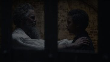 John Brown (Ethan Hawke) with his arms on Onion's (Joshua Caleb Johnson) shoulders in a darkened jail cell seen through the bars