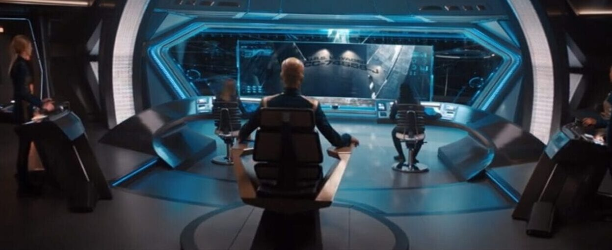 The Discovery bridge seen from behind with Saru (Doug Jones) in the center in the captain's chair Voyager is visible in the viewscreen