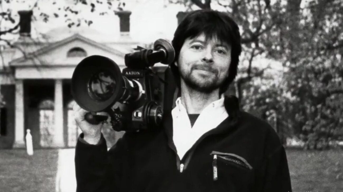 Black and White photo of a young Ken Burns holding a large film camera over his shoulder, standing in front of a white house