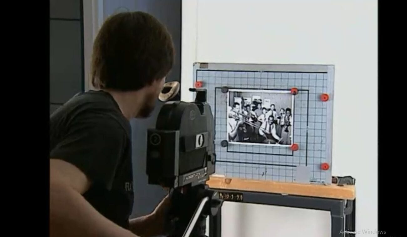 Ken Burns holds a camera on tripod pointed at a photograph set to be scanned