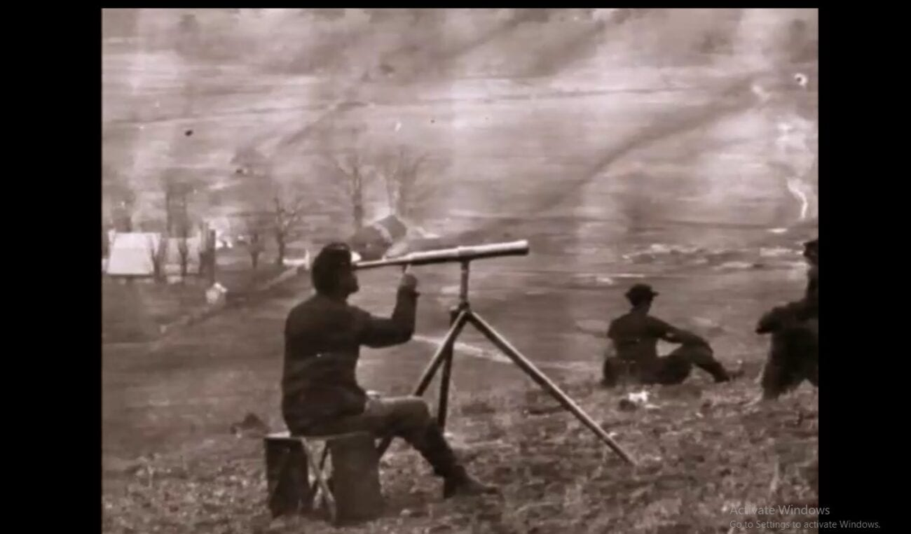 A sepia-toned photograph of a Black soldier sitting at a telescope on a battlefield. Another man sits in front of him on the ground.