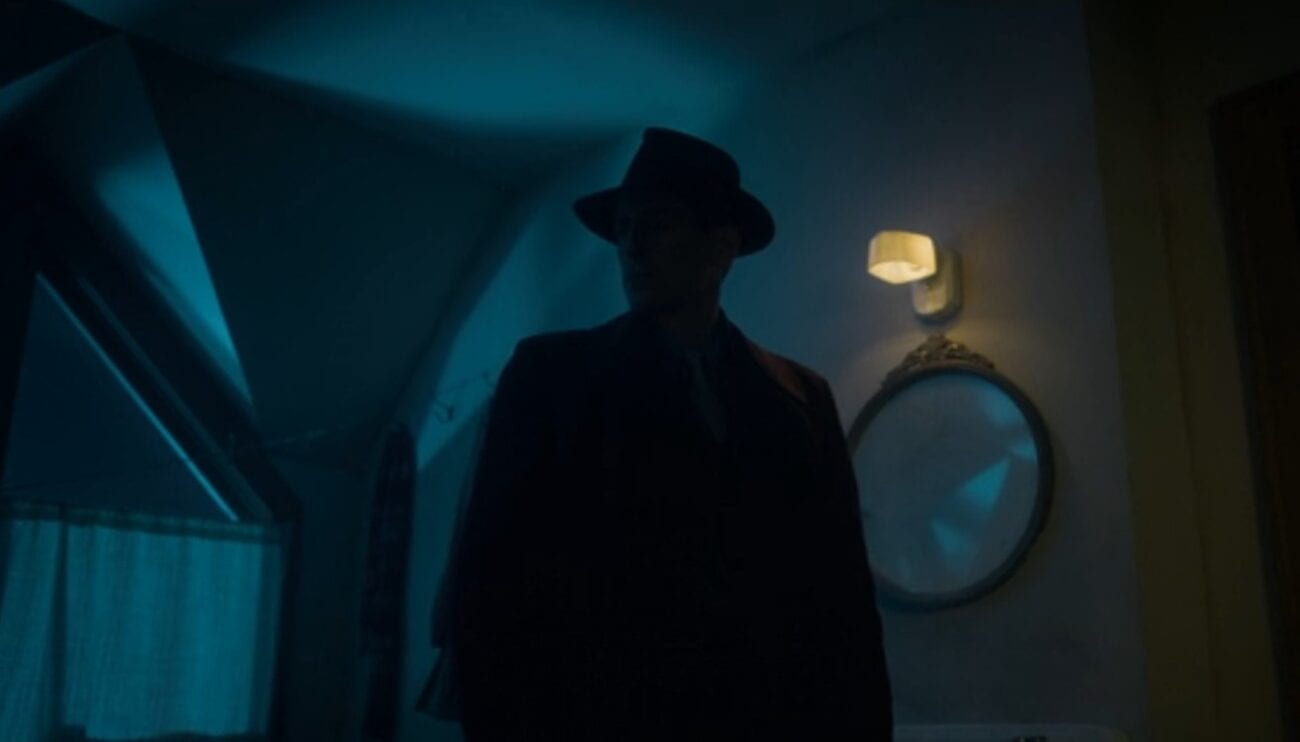 A shadowy fedora-wearing silhouette in the foreground of a blue-tinted attic room as an example of the noir-inspired cinematography on Fargo.