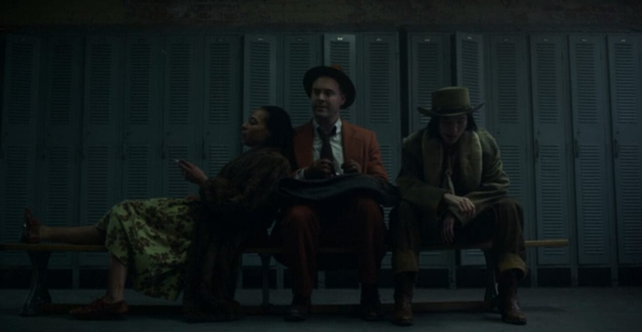 Zelmare, wearing a fur coat and green dress, leans against Detective Weff in an orange suit on a locker room bench. Swanee sits on his other side wearing a cowboy hat and looking at the floor.