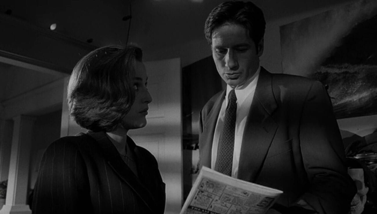 A black and white image of Mulder & Scully looking down at a comic book.