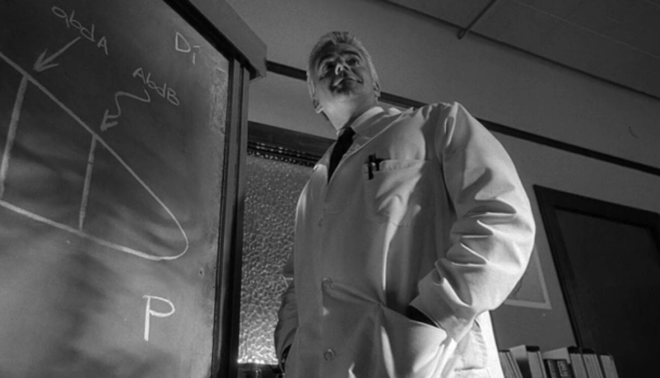 A scientist in a white lab coat standing next to a chalkboard.
