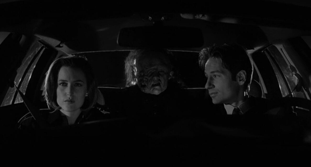 Agent Mulder drives and looks over at Scully in the passenger seat looking forward. In the backseat is The Great Mutato.