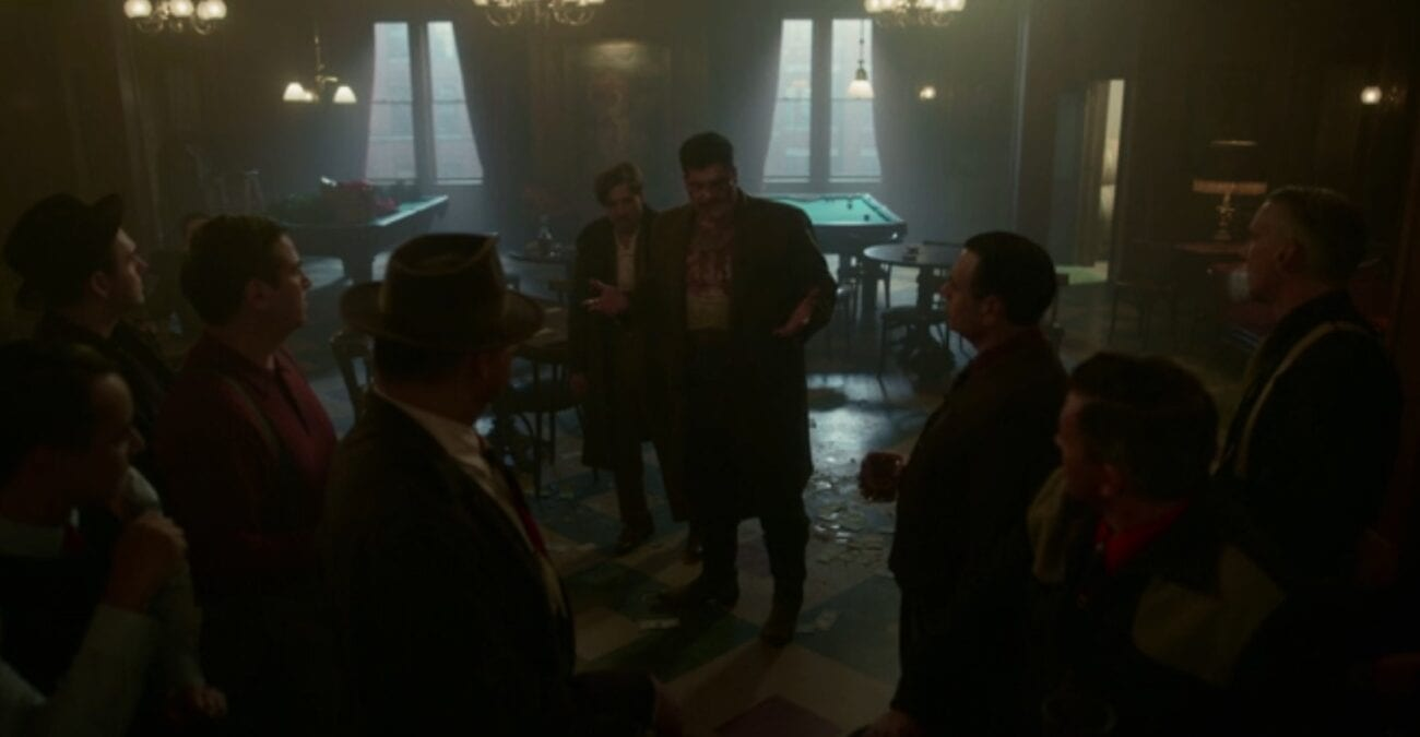 In a dimly lit bar Gaetano, bloody and bruised, addresses his gang with his brother, Josto, stands behind him confused and disheveled.
