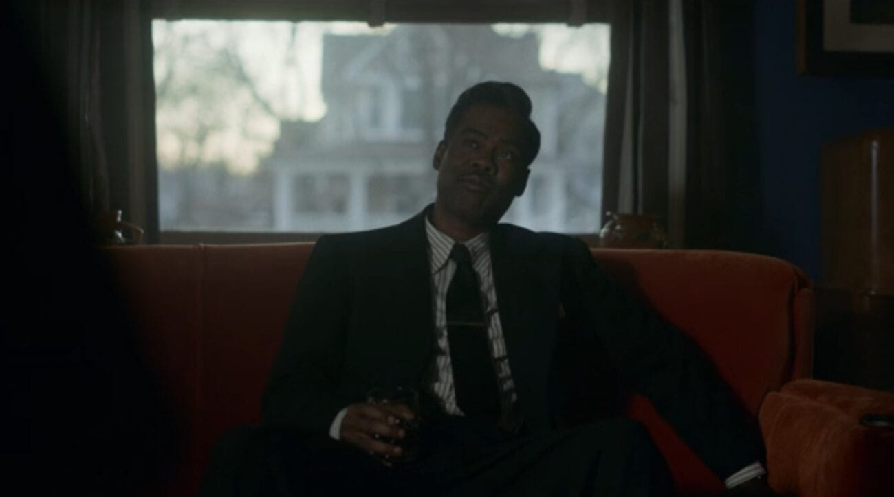 Loy Cannon, played by Chris Rock, looks incredulous as he listens to Deafy (out of frame) on a red sofa. the sunset and neighboring house visible through a large window in the background.